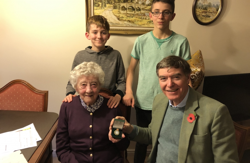 Philip Dunne MP presenting the Women's Land Army badge to June Lee with her foster grandchildren Zac and Marcus Clements