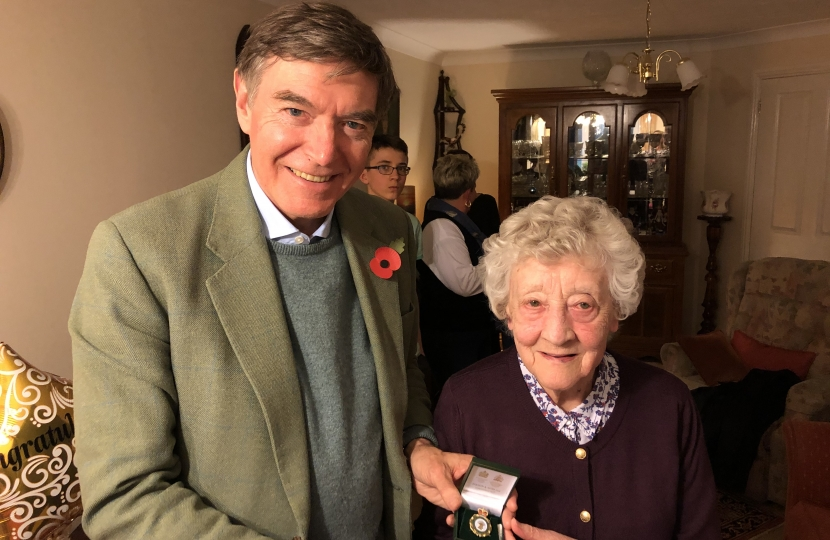Philip Dunne MP presenting the Women's Land Army badge to June Lee